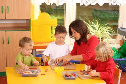 Foto von einer Erzieherin mit drei Kindern beim Spielen