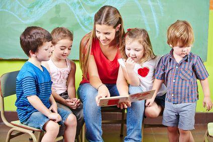 Foto: Kinder mit Erzieherin lesen Buch im Kindergarten - � Robert Kneschke - Fotolia.com