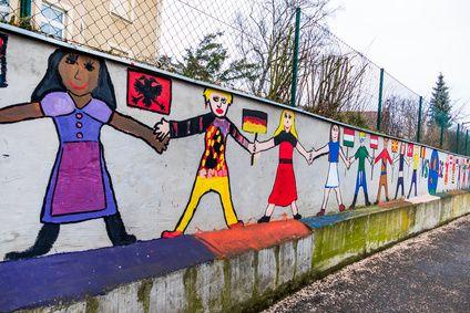 Auf eine Schulmauer gemalte Kinder verschiedener Nationen