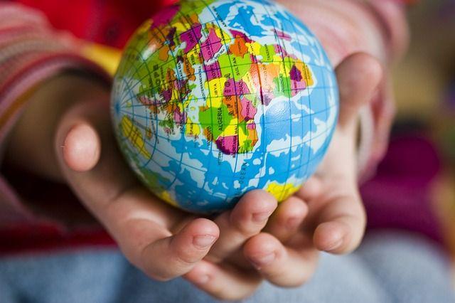 Foto einer Kinderhand mit Weltkugel